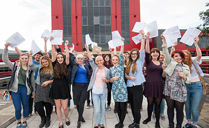 photo of students cheering whilst holding their a level results
